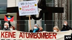 Aktivis anti-nuklir dari ICAN (Kampanye Internasional untuk Menghapuskan Senjata Nuklir) dan inisiatif perdamaian lainnya menggelar protes dengan 51 bendera negara yang meratifikasi Perjanjian PBB untuk Larangan Senjata Nuklir di depan kantor Kanselir di Berlin, 22 Januari 2021.