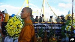 Earlier today, in Cambodia, a group of monks and officials pray for victims near the site where people stampeded during Monday's water festival in Phnom Penh.