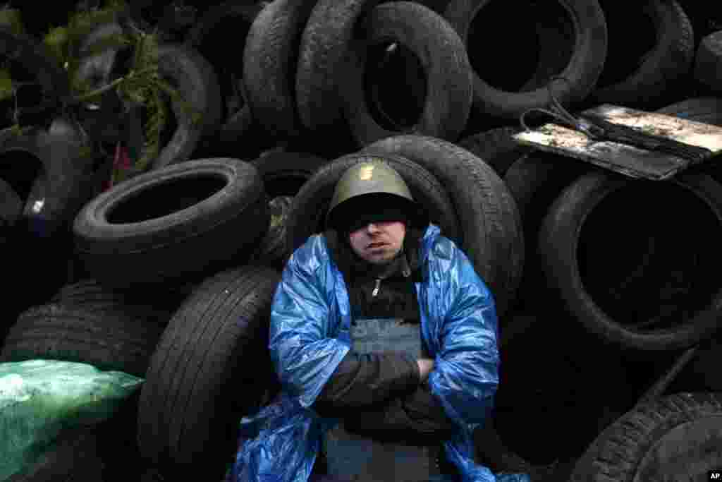 An anti-government protester sits and rest on a barricade at Independence Square in Kyiv, Feb. 21, 2014.
