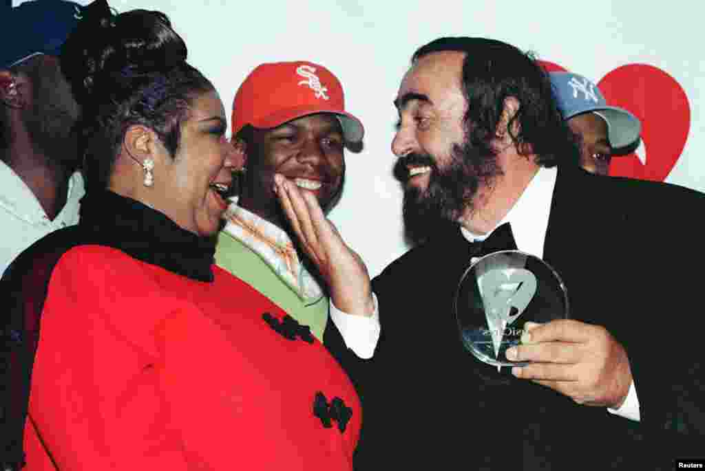 Singer Luciano Pavarotti gestures towards singer Aretha Franklin during a photo opportunity at the 1998 MusiCares benefit dinner in New York, Feb. 23, 1998.
