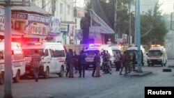 Bezbednosne snage Somalije obezbeđuju mesto eksplozije automobila bombe, dok vozila hitne pomoći čekaju kako bi se ukazala ponoć povređenima u oblasti poznatoj kao Četvrti kilometar u Mogadišu, Somalija, 31. januara 2021. (RojtersS/Feisal Omar)