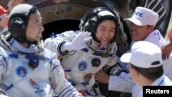 FILE - Liu Yang, center, China's first female astronaut, waves next to her comrade Jing Haipeng, in this June 29, 2012 photo.