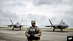 Một thành viên cảnh sát quân sự Mỹ đứng phía trước máy bay chiến đấu F-22, bay ngày 25 tháng 4 năm 2016 đến căn cứ không quân Mihail Kogalniceanu, gần cảng Biển Đen của Constanta ở phía đông nam Romania.