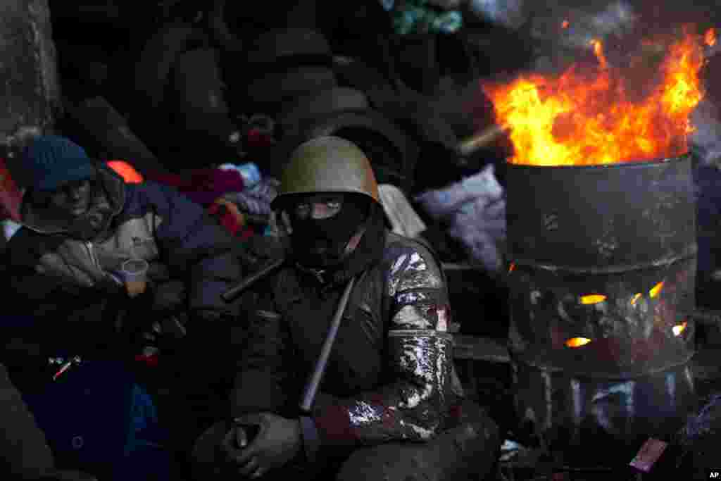 An opposition supporter looks on as he warms himself next to a fire in a barricade near Kyiv's Independence Square, Jan. 31, 2014.