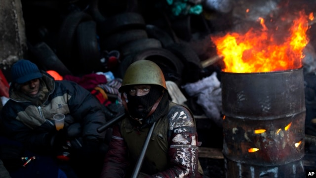 An opposition supporter warms himself next to a fire in a barricade near Kyiv's Independence Square, Jan. 31, 2014.