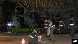 Cảnh sát và nhân viên pháp y Thái Lan điều tra phía trước trung tâm mua sắm Siam Paragon sau vụ nổ bom.