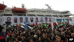 People, holding Turkish and Palestinian flags, cheer as the Mavi Marmara ship, in the background, the lead boat of a flotilla headed to the Gaza Strip which was stormed by Israeli naval commandos in a predawn confrontation in the Mediterranean May 31, 201