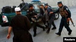 阿富汗警察抬着一个在喀布尔被炸伤的男子 (2017年10月31日)