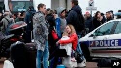 Los viajeros esperan fuera del aeropuerto de Orly, al sur de París, el sábado, 18 de marzo de 2017. Un hombre fue asesinado a tiros después de intentar apoderarse del arma de un soldado que custodiaba el aeropuerto de París Orly, provocando una evacuación parcial de la terminal.