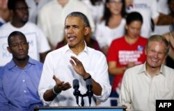 FILE - Florida Democratic gubernatorial nominee Andrew Gillum, left, and Senator Bill Nelson (D-FL), right, listen to former President Barack Obama as he addresses the media and supporters as they stump for votes at a rally in Miami, Florida, Nov. 2, 2018.