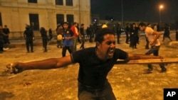 2013年7月15日,在埃及首都开罗市中心,反对穆尔西总统的群众向支持穆尔西总统的群众投掷石头。