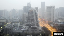 FILE - A building crumbles during a controlled demolition to make way for a new commercial center in Xi'an, Shaanxi province, China.