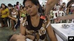 Seorang perempuan Filipina sedang diberi suntikan KB. Menurut Laporan Dana Kependudukan PBB (UNFPA) investasi empat miliar dolar per tahun akan memungkinkan perempuan di negara berkembang mendapat informasi mengenai reproduksi yang akan menyelamatkan nyaw