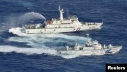 A Japanese Coast Guard patrol ship (C) sprays water at a fishing boat from Taiwan, as Taiwan's Coast Guard vessel (top) sprays water near the disputed islands in the East China Sea, September 25, 2012.