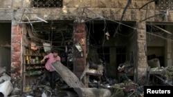 19일 시리아 이들리브 주 시장 지역에 공습이 있은 후, 한 남성이 붕괴된 상점 건물을 수색하고 있다.