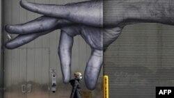 一位女士戴着口罩走过纽约市中城一座大楼的巨手壁画。(2020年4月22日)
