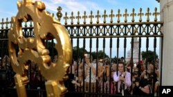 Warga berkerumun di depan Istana Buckingham untuk membaca pengumuman tentang kelahiran Pangeran Kerajaan Inggris, putra pertama Pangeran William dan istrinya Kate, pada jam 4: 24 sore waktu setempat (22/7).