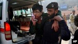 Un guardia de seguridad ayuda a un estudiante herido luego del ataque a la escuela militar en Peshawar, Pakistán.