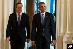 FILE - President Barack Obama and British Prime Minister David Cameron arrive for a joint news conference in the East Room of the White House in Washington, Friday, Jan. 16, 2015.