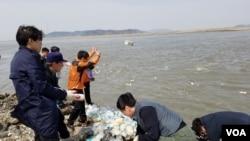 탈북자 단체들이 2일 강화도에서 쌀과 이동식저장장치(USB) 등이 들어 있는 페트병 500개를 바다에 던지고 있다.
