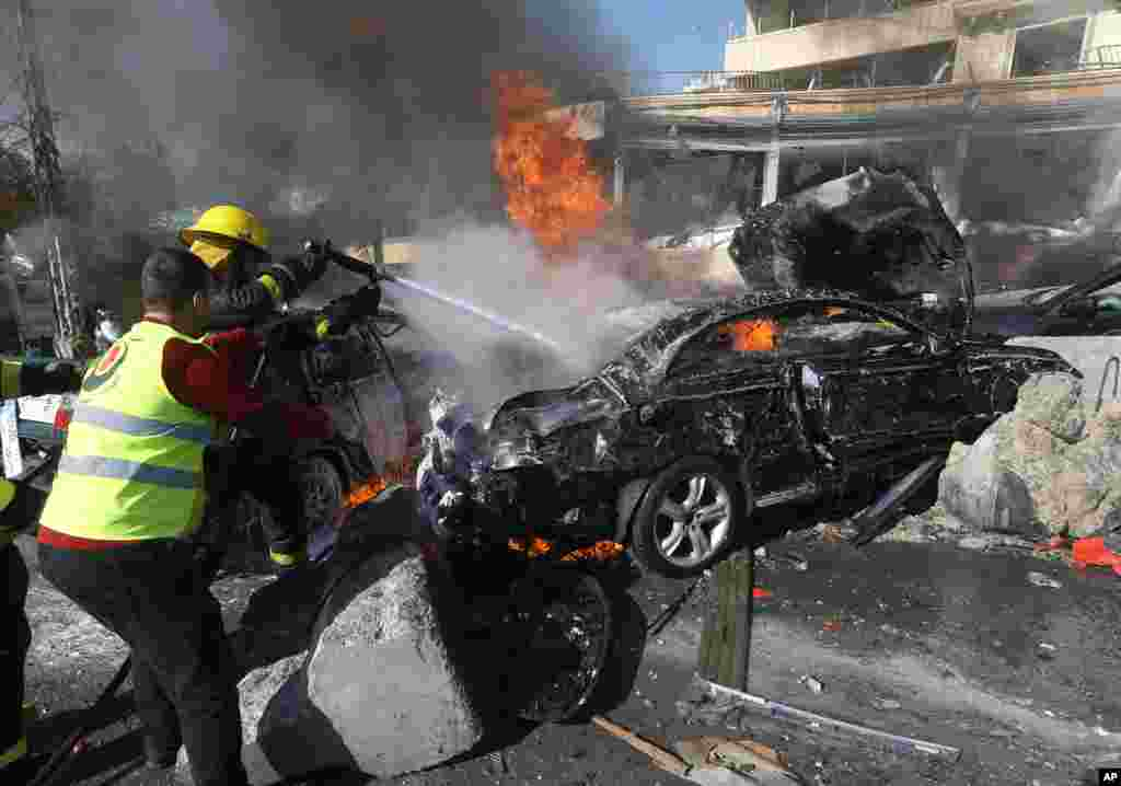 Lebanese firefighters extinguish a burning car at the site of an explosion near the Kuwaiti Embassy and Iran's cultural center, in the suburb of Beir Hassan, Beirut, Lebanon, Feb. 19, 2014.