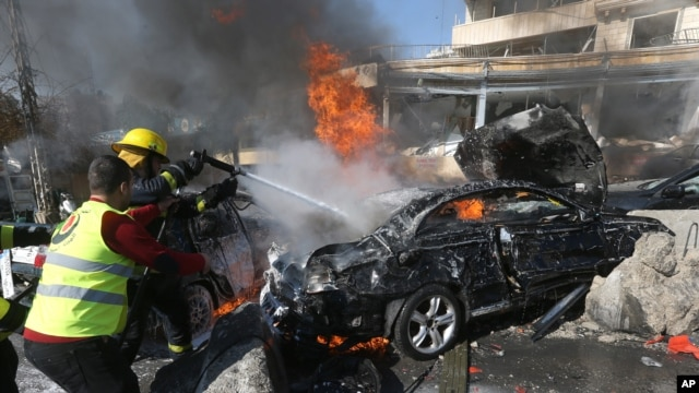 Lebanese firefighters extinguish a burning car at the site of an explosion near the Kuwaiti Embassy and Iran's cultural center, in the suburb of Beir Hassan, Beirut, Feb. 19, 2014.
