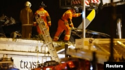 Rescue workers examine the wreckage of police helicopter that crashed on roof of the Clutha Vaults pub, Glasgow, Scotland, Nov. 30, 2013.