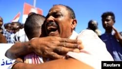 Warga Sudan berpelukan untuk merayakan keputusan pengadilan menghukum mati 27 anggota pasukan keamanan di Khartoum, Senin (30/12).