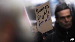 图为一名抗议者12月10日的国际人权日在柏林手持标语抗议种族主义、为全人类呼吁人权的情形。