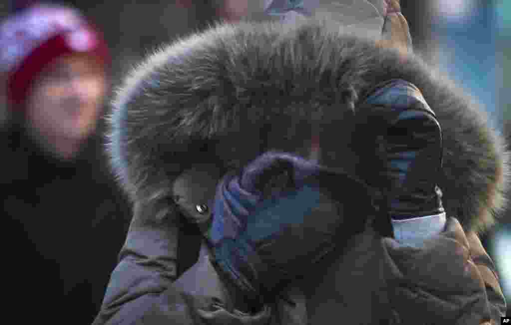 A pedestrian covers up against single digit temperatures in New York, Jan. 7, 2014.