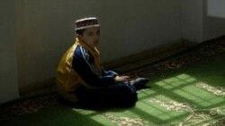 یک کودک تاجیک در مسجدی در دوشنبه برای نماز آماده می شود