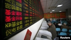 Investors look at computer screens showing stock information at a brokerage house in Shanghai, China, April 21, 2016.