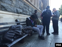 A man rests next to a statue of the homeless Jesus outside Catholic Charities in Washington. (K. Gypson/VOA)