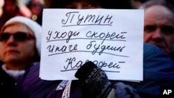 """星期六的抗议集会上一俄罗斯民众手举""""普京赶快离开否则你会和卡扎菲的下场一样""""的标语"""