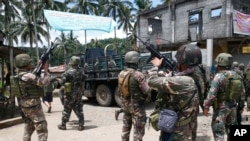 FILE - In this May 30, 2017 photo, Philippines government troops prepare to head to the frontline as fighting with Muslim militants in Marawi city continued in southern Philippines.