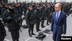 FILE - Ukrainian Prime Minister Arseniy Yatsenyuk (R) inspects servicemen and government defence forces outside Kyiv, Sept. 30, 2014.