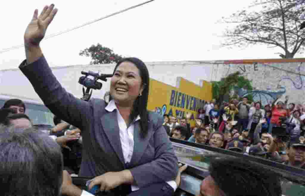 La candidata presidencial, Keiko Fujimori, saluda a la gente que rodea la mesa electoral.