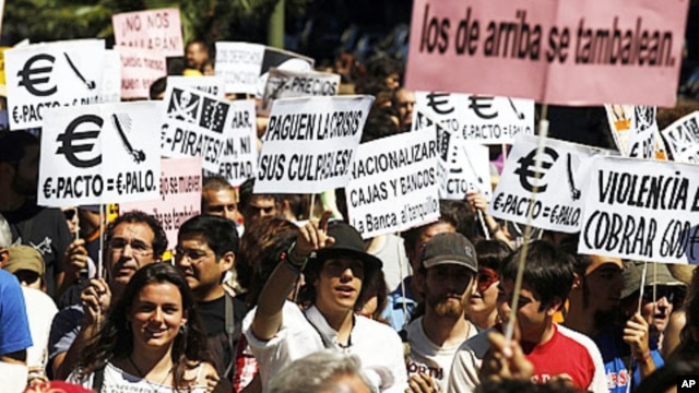 Demonstrators holding placards march towards the building of the Spanish parliament in Madrid, June 19, 2011
