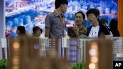FILE - People view housing models on display during the China Property and Investment Show in Beijing, Sept. 21, 2012.