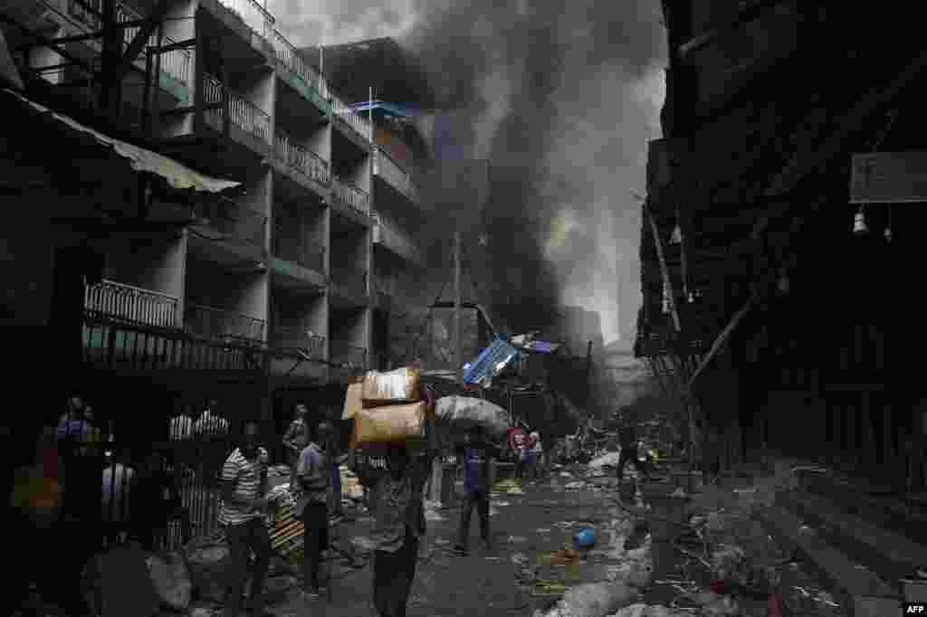 People carry goods salvaged from a fire that broke out in a section of the Balogun market in Lagos, Nigeria.