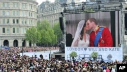 Royal supporters watch Britain's Prince William kissing his wife Kate, Duchess of Cambridge on a giant screen in Trafalgar Square in central London, after the wedding ceremony, on April 29, 2011.