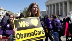 "FILE - Holding a sign saying ""We Love ObamaCare,"" a supporter of health care reform rallies in front of the Supreme Court in Washington, D.C., March 27, 2012."