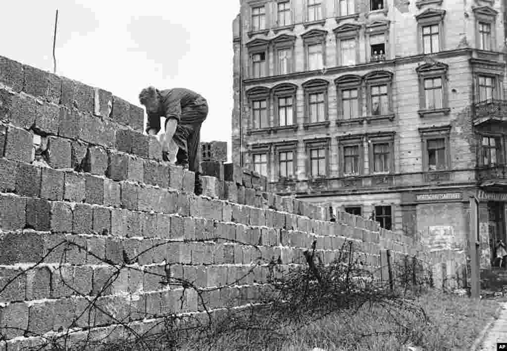 ARCHIV - Ein Ostberliner Polizist arbeitet am 9. Oktober 1961 an der Berliner Mauer. Am Donnerstag, den 13. August 2009, jaehrt sich der offizielle Tag des Mauerbaus zum 48. Mal. (AP Photo/Archiv) * NUR S/W * --- FILE - In this Oct. 9, 1961 file photo an