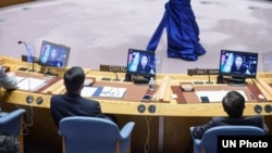 FILE - Shaharzad Akbar (on screens) of the Afghanistan Independent Human Rights Commission addresses a Security Council meeting, Aug. 6, 2021. She again spoke at the U.N. on Sept. 24, 2021, urging global leaders to pressure the Taliban to let girls go to school.