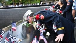 Retired Paramedic Chief Charlie Wells kisses the name of a relative killed in the attack on the World Trade Center at the National September 11 Memorial in New York on the 20th anniversary of the attacks, Sept. 11, 2021.
