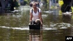Một phụ nữ băng qua 1 con đường ngập lụt ở Bangkok, 28/10/2011