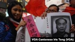 手持《香港民族論》及支持港獨標語參與遊行的梁小姐(左)表示,擔心這本書會成為禁書