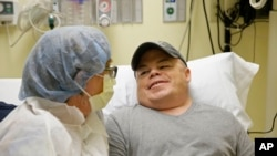 In this Nov. 6, 2017 photo, Brian Madeux sits with his girlfriend Marcie Humphrey while waiting to receive the first human gene editing therapy at the UCSF Benioff Children's Hospital in Oakland, Calif.