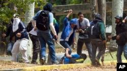 Un estudiante sufre una paliza en la Universidad Central de Caracas a manos de grupos pro gubernamentales.