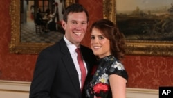 FILE - Britain's Princess Eugenie and Jack Brooksbank pose for the media in the Picture Gallery at Buckingham Palace after they announced their engagement in London, Jan. 22, 2018.